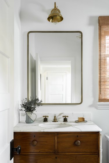white bathroom with deck-mounted faucet on wood vanity and marble countertop