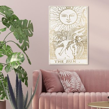 The Sun Tarot Luxe' Astronomy and Space Wall Art Canvas Print - Gold, White - on pink wall above pink couch with pillows