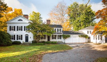 white garage door on colonial home surrounded by trees