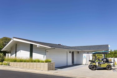 white garage door on ranch style home with golf cart out front