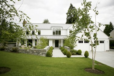 white garage door surrounded by greenery