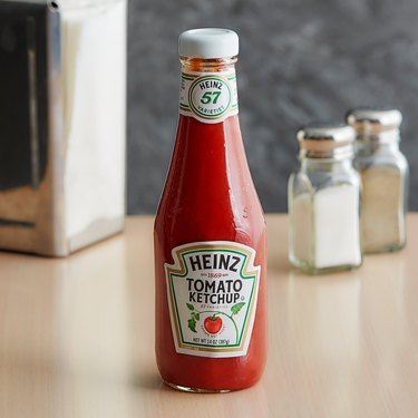 heinz ketchup bottle on wood table with salt and pepper