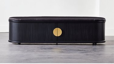 black bedroom storage bench with cushioned top and brass pulls