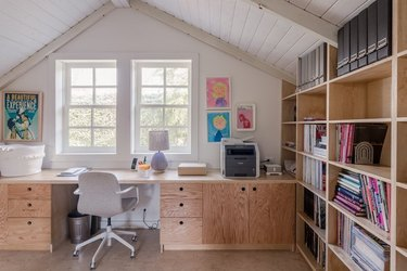 How To Organize a Bookshelf in room with desk, white arched ceiling, windows, desk chair, lamp, books, art.
