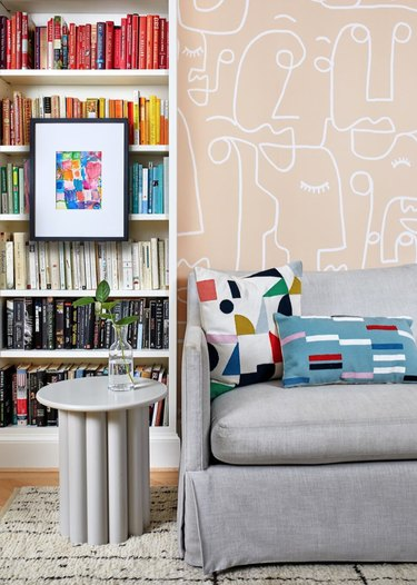 How To Organize a Bookshelf in Living room with pale pink patterned wallpaper, color coded book shelves, gray couch, white modern end table, colorful throw pillows, art.