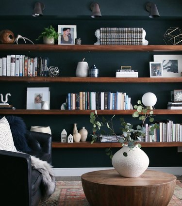 How To Organize a Bookshelf in Dark green room with wood book shelves, wood coffee table, vase with flowers, black leather chair, books, art, lighting.