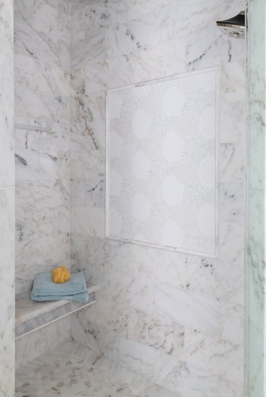 Marble tile in a shower with floral tile panel and bench