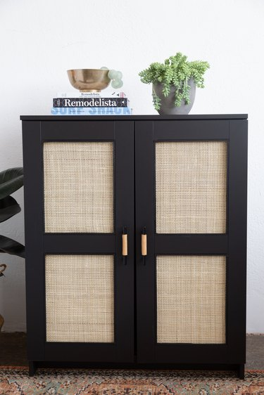 Black IKEA cabinet with cane webbing on door