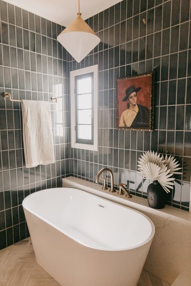 modern bath fixtures in blue-green tiled bathroom with freestanding tub and art on the wall