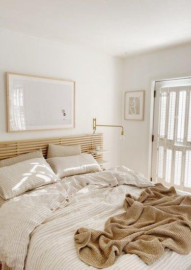 Sylvia Tribel  bedroom with IKEA headboard and brass wall sconces