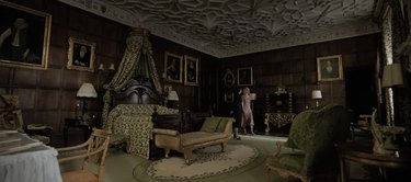 master bedroom with wooden finish walls and dark green decor
