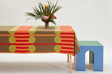 table with plant and colorful, patterned tablecloth, with blue stool nearby