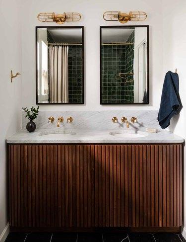 Midcentury Modern Bathroom Sink, brass wall mount faucets, mirrors, sconces, wood vanity, towel.