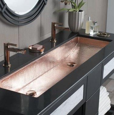 copper industrial bathroom sink with black vanity