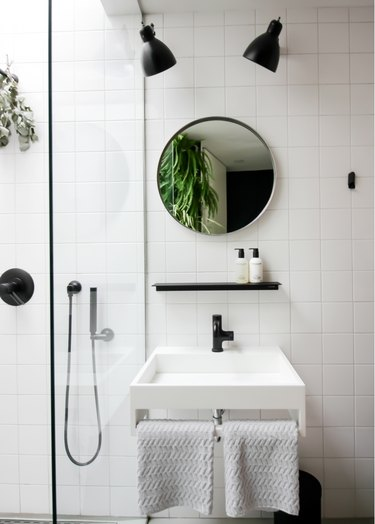 small minimalist bathroom with round vanity mirror and black fixtures