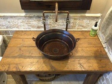 copper industrial bathroom sink on wood counter