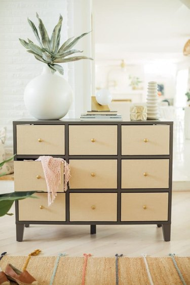 IKEA dresser with rattan drawers and large plant in white vase on top