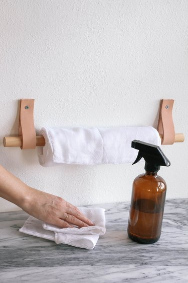 DIY reusable fabric paper towels hanging on wood and leather paper towel holder