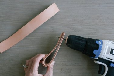 Folding leather strip in half and drilling pilot hole through ends
