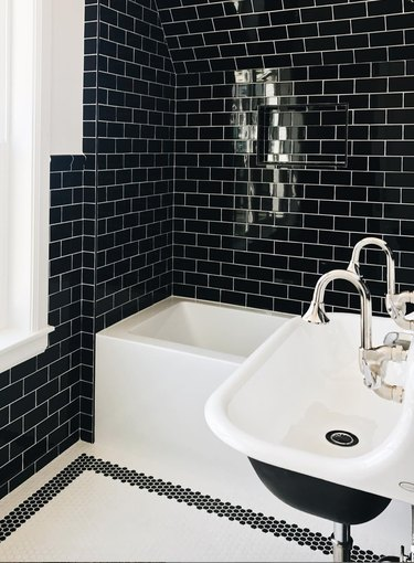 black subway tile in small bathroom with black and white accents