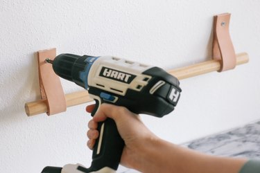 Drilling screws to attach leather straps to wall