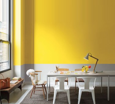 yellow and gray wall with long table and white chairs