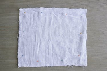 Two fabric squares pinned together