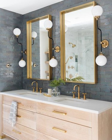 blue subway tile with trio of architectural sconces