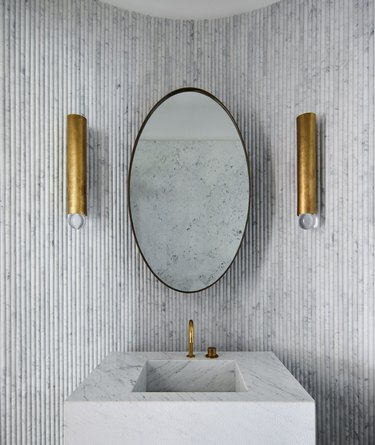 block marble bathroom sink against fluted marble wall