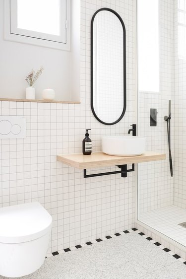 White bathroom with modern vanity, round vessel sink, black faucet, black framed oval mirror, white tile and Scandinavian Bathroom Storage Ideas.