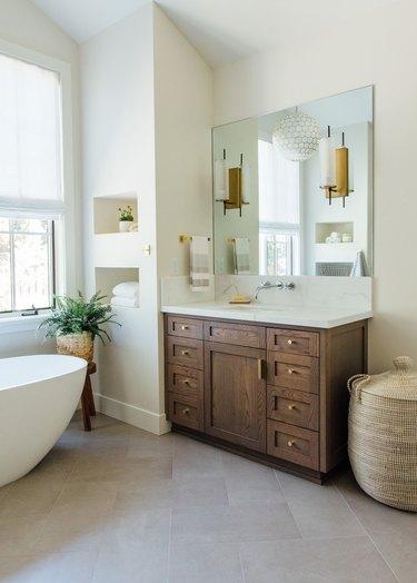 Farmhouse bathroom storage designed by Michelle Lisac Interior Design with baskets and under the sink storage