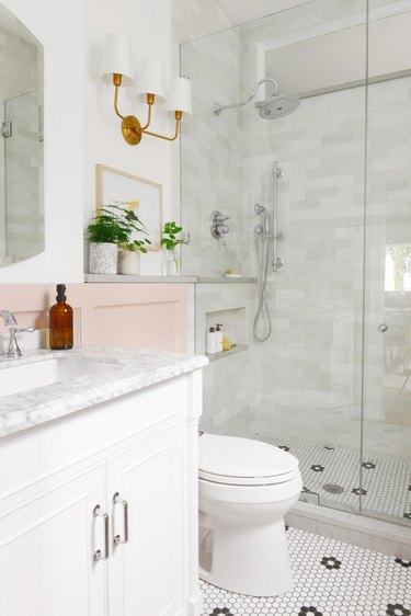 Polished chrome shower fixtures in tile shower in pink and white bathroom