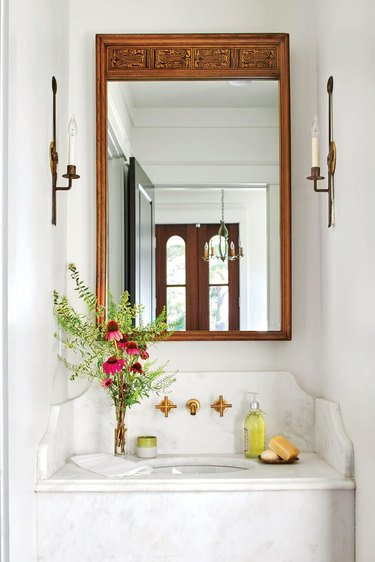 French country bathroom sink with marble vanity, candle sconces, vintage mirror, wall mounted faucet, flowers, soaps.