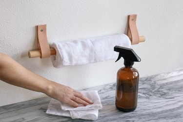 Fabric towels hung on leather and wood holder