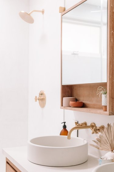 Brass Bathroom Faucet in boho bathroom with circular basin sink and wall mounted brass taps
