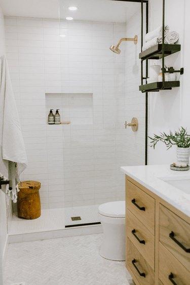 black bathroom shelving above toilet next to wooden vanity cabinet