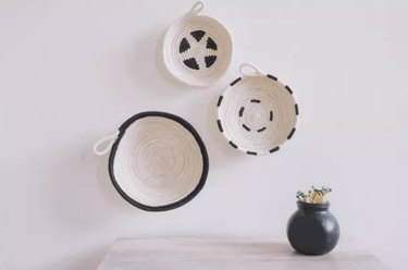 Painted black and white rope bowls hung on wall
