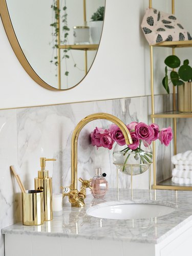 Brass Bathroom Faucet in luxury marble bathroom with brass faucet and decor