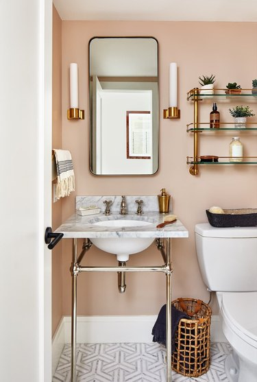 pink powder room with glass bathroom shelving above the toilet and next to a vanity mirror