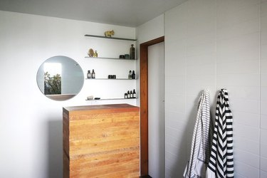 wooden cabinet, mirror, and minimalist floating bathroom shelving