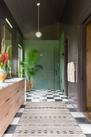 sophisticated dark bathroom with gray walls and green tiled bohemian shower