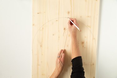 Hand making drawing on wood board