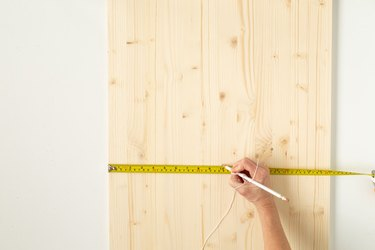 Hand with measuring tape on wood board