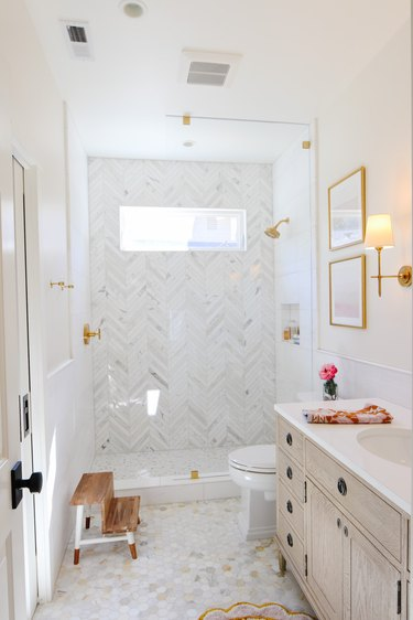 Marble tile in a shower with herringbone shower wall and window