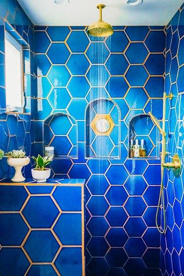 hexagon shaped blue shower tile in bohemian bathroom