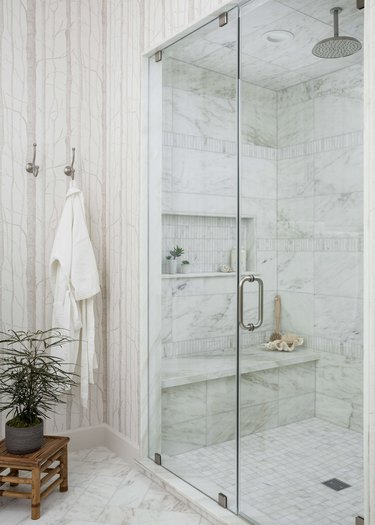 Marble tile in a shower with bench and storage in modern bathroom
