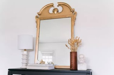Gilded mirror on shelf