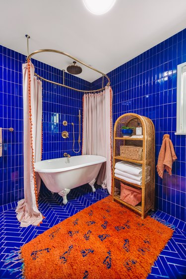 Floor to ceiling blue shower tile in modern bathroom with orange rug
