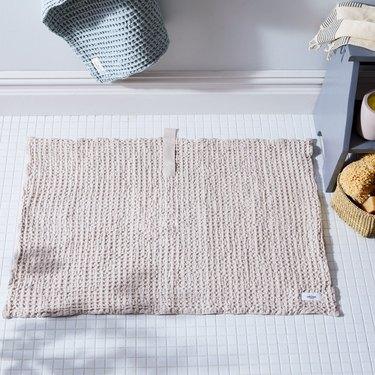 Food52 waffle bath mat on a white mosaic tile floor