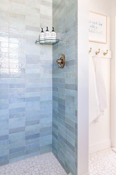 Blue shower tile in varying shades of subway tile in coastal bathroom